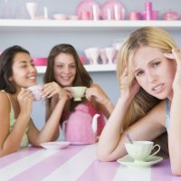 Two young women enjoying a tea party while one sits apart