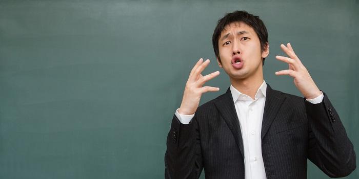 両手を上げる講師